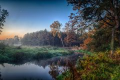 River in the fog, just before sunrise. A warm glow in the clouds from the first rays of the sun. The Grabia River in central Poland immediately after the royalty free stock images