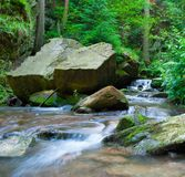 River in forest. With big stones. Little waterfall taking with long time royalty free stock image