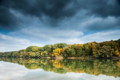 River and forest with dark sky in autumn Stock Photo