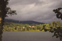 River and forest with village and mountain in clouds on other bank. Trees with ivy foreground with lake and village on other side. Rural landscape with stock image