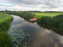 River in Friesland. Small river with a boat in Friesland The Netherlands Stock Photo
