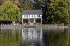 River front reflecting white home. On Bend's Deschutes River, Mirror Pond, this pretty little white home is reflected like a watercolor Stock Photos