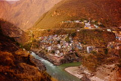 River Ganges flowing among Himalayan moutains near inhabited banks. Houses on the banks of the river Ganges at the Himalayan mountains. Rishikesh. India stock image