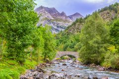 The River Gave de Gavarnie. Image of a stone bridge over the River Gave de Gavarnie few kilometers downstream of the Cirque de Gavarnie in Pyrenees Mountains stock photo