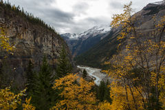 River Between Giant Mountain Ranges. A river meandering through a huge valley sided by massive rocky mountains. Golden leafed fall trees in the foreground Stock Photography