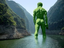 River with green giant. Green giant seen from behind walking in a river Royalty Free Stock Photography