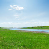 River in green grass and clouds in blue sky Royalty Free Stock Photo
