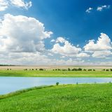 River in green grass and clouds in deep blue sky Stock Photo