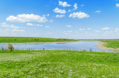 A river in green grass under a blue sky with clouds. View of a river in green grass under a blue sky with clouds Stock Photo