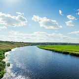 River in green landscape and cloudy sky Stock Images