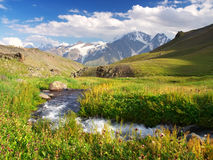 River on green meadow. Amongst mountains Stock Photos