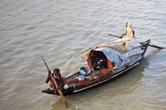 The river gypsy couple. A Bangladeshi river gypsy old man and woman fishing on her boat on the Meghna river in Vola District, Borishal Stock Photography