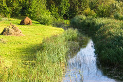 River and hayfield. Small river and hayfield with two haystacks Royalty Free Stock Photography