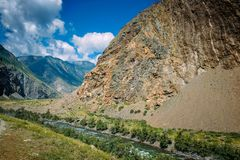 River among the high mountains. Picturesque landscape of rocky Altai mountains and Chulyshman river. Mountain range, river, green. Coast, blue sky and white royalty free stock images