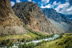 River among the high mountains. Picturesque landscape of rocky Altai mountains and Chulyshman river. Mountain range, river. Green coast, blue sky and white royalty free stock photography