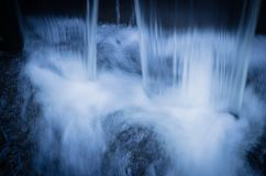 River during high water flow. Taken with a slow shutter speed to smooth out the flow of the water as is rushes by Stock Image