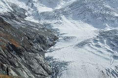River of Ice. Man stands on mountain overlooking a glacier in the swiss alps Royalty Free Stock Photos