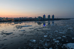 River ice city debacle evening. Scenic night view on the breaking of the ice on the river with a fast flowing on the background of city with lights and Royalty Free Stock Photo