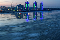 River ice city debacle evening. Scenic night view on the breaking of the ice on the river with a fast flowing on the background of city with lights and Royalty Free Stock Photos