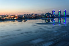 River ice city debacle tracks. Scenic night landscape with the breaking of the ice on the river with a fast flowing on the background of city with lights and Royalty Free Stock Photography
