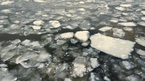 River ice flow in winter, snow falling down, aerial top down view stock video