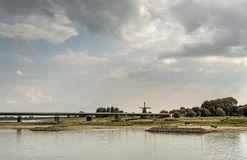 River IJssel with bridge and windmill under cloudy sky. Overijss. River IJssel with bridge and windmill under a cloudy sky. Overijssel, Netherlands Stock Photos