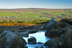 River on Ilkley Moor. A small stream Blackstone Beck runs over rocks on Ilkley Moor, in West Yorkshire, England, in early morning. The village of Denton can be stock image