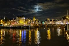 River by illuminated cityscape against sky at dusk. A night view from Amsterdam stock photography