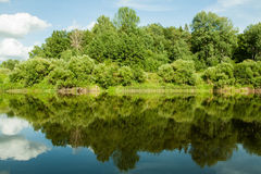 River and its banks. Trees along both sides of the water. Sky is cloudy. Stock Photography