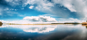 River Or Lake Landscape With Reflections Of Cloudy Sky In Water. Stock Photography