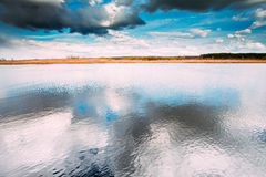 River Or Lake Landscape With Reflections Of Cloudy Sky In Water. Royalty Free Stock Images