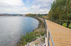 River lake water pier wooden catwalk bank way path cycling track urban park city horizon Royalty Free Stock Photo