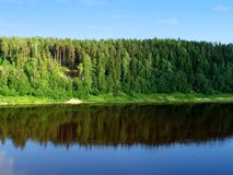 River land 1. A river, a forest on a hill reflecting in water and a blue sky Royalty Free Stock Image