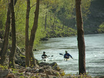 River landscape and canoeing. Sping awakes, beautiful river landscape, silhouettes of two boys on canoe practice Stock Image