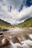 River landscape in drakensberg with dramatic clouds Royalty Free Stock Image