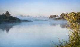 River landscape in early morning with mystery fog. Beautiful sunrise on river bank in early morning royalty free stock photography