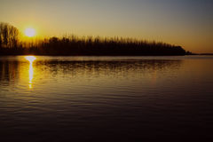 River landscape. Sunset on a lake with trees silhouette Stock Photos