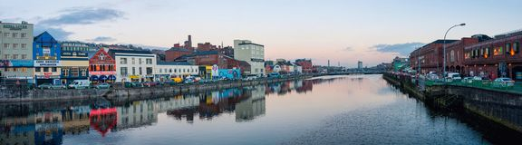 River Lee in Cork, Ireland. CORK, IRELAND - DECEMBER 5, 2014: Panoramic view of River Lee quays in the city center with many restaurants, shops, bars and car Royalty Free Stock Photos