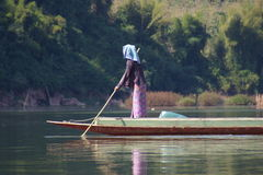 River Life 2. Asian woman fishing on a river from a canoe Stock Photos