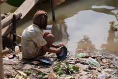 River life. Lady washing dishes in the river Stock Photo