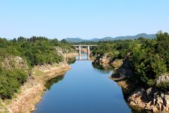 River with low summer water levels flowing towards concrete bridge surrounded with lush green forest vegetation. River with low summer water levels and visible royalty free stock images
