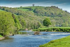 The river Lune near Lancaster below wooded slopes. Stock Photography