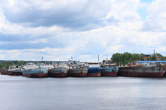 River with many rusty cargo ships and sky with clouds Royalty Free Stock Images