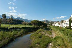 River in Marbella. With mountains, palmtrees, and apartments Royalty Free Stock Photos