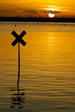 River marker silhouetted against the setting sun. Focus on far river bank Stock Photo