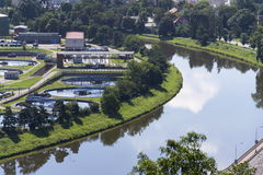 River meandering around sewage water treatment plant Stock Image