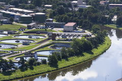 River meandering around sewage water treatment plant Stock Images