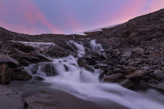 River of melt water from glacier and pink sunset background. Waiting for the sunset giving this beautiful pink glow over the Ruothesjiegna glacier, Sarek royalty free stock image