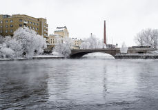 River in the middle of the city on a cold and cloudy winter day Stock Image