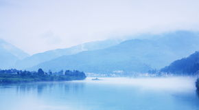 River in mist. China Sichuan mountain village nestled on the river mist thrown Stock Photo